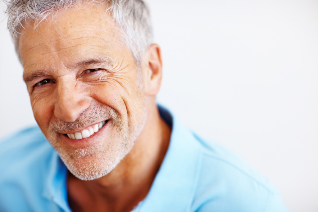 Closeup portrait of a happy mature man on white background